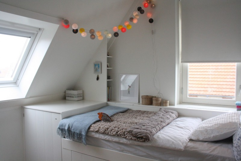 contemporary kids's bedroom design attic loft bed in white simple white book rack white half window shad white comforter white linen hand knitted blankets elevated skylight