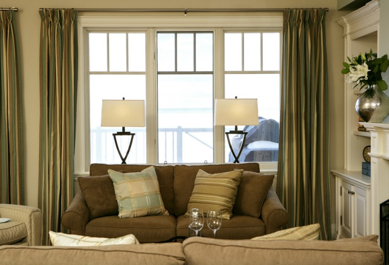 contemporary living room with comfy reclaining chairs full length half curtains soft beige walls white buffet