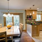 Contemporary Open Kitchen With Light Brown Flooring In The Kitchen With Brown Cabinet And Black Counter Top, Darker Brown Flooring For The Dining Area With Wooden Dining Set And Chandelier