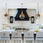 Contemporary White Cabinet Golden Glass Pendant Lights Marble Backsplash Marble Counter Top Dark Hood Grey Bar Stools