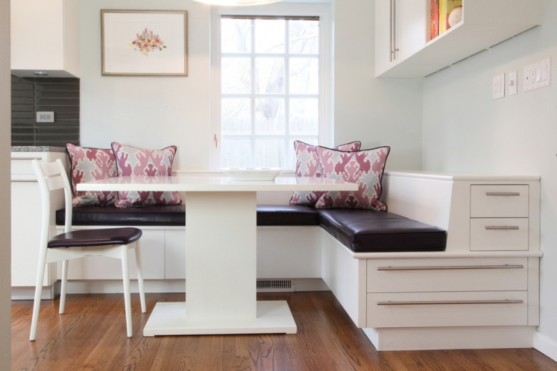 corner banquette seating with white wooden bench with black leather cushion, pink pillows, white wooden table and one white wooden chair with black leather cushion