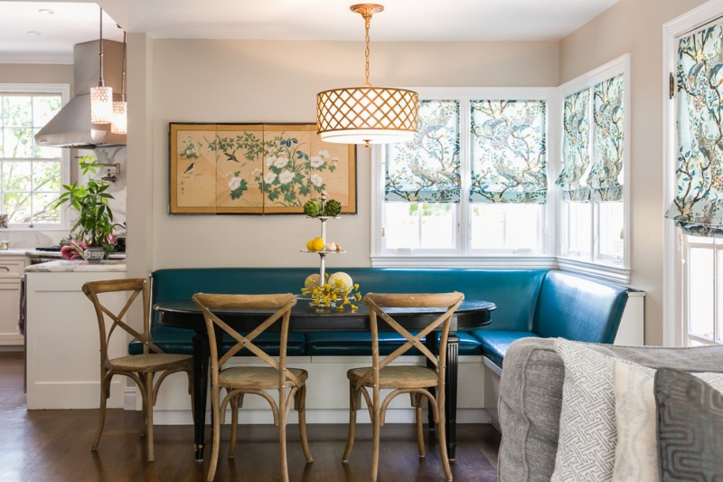 corner banquette seating with white wooden bench with blue cushion, dark wood table, raw light brown wood chairs