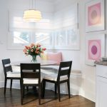 Corner Table Set With White Bench With White Cushion And Pink Pillow, Black Chairs With White Cushion, Pendant Lamp, Near A Window With White Curtain
