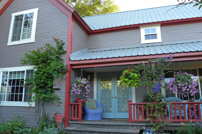 cottage's exterior with grey siding walls blue painted glass front door blue trimmed glass windows blue porch furniture and short & red railing system