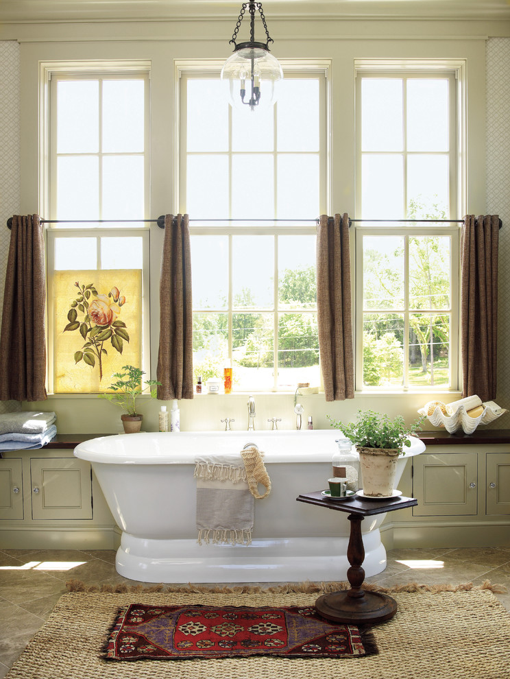 country style bathroom with free standing tub in white stationary with extra storage small side table slanted floors in beige beige walls brown half window curtains
