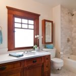 Craftsman Bathroom With White Hexagonal Tiles In Floor, Stoney White Wall In The Shower Area, White Painted Walls In The Toilet And Wastafel Area, Dark Brown Cabinet With White Counter Top