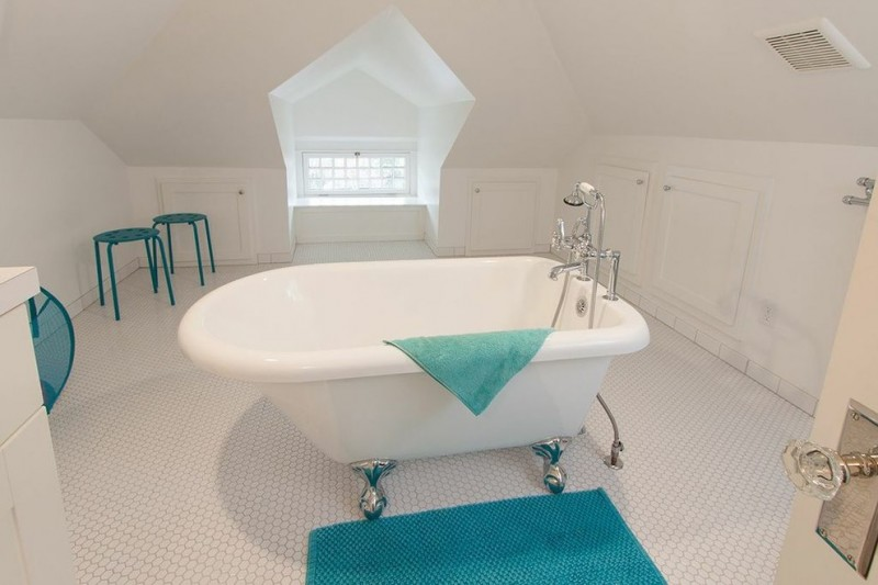 craftsman bathroom with white small tiles in flooring, white walls and vaulted ceiling, white cabinet