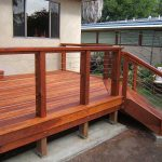 Dark Finishing Wooden Deck Idea With Thin Stainless Steel Wire Railing System