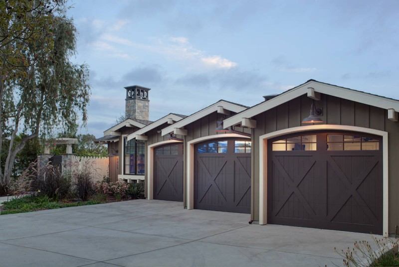 dark garage wooden three garage cream trim bronze siding outdoor lights