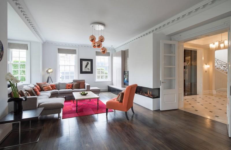 dark hardwood floor u shaped sofa orange chair whitel flat panel cabinet contemporary fire place