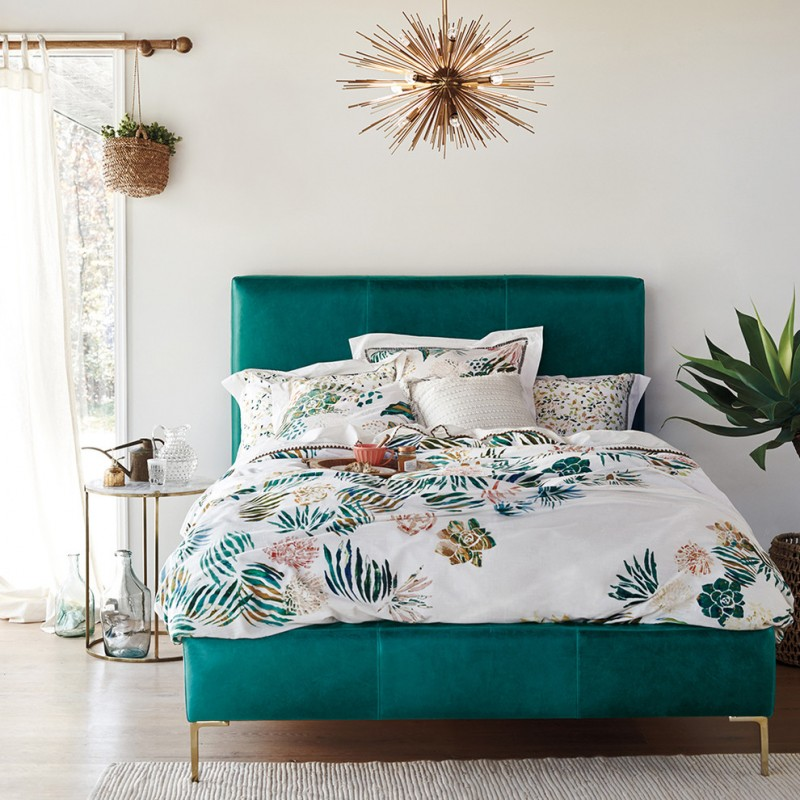 dark turquoise bed with headboard colorful bed sheet with floral motif floral themed pillow shams dark wooden floors textured white area rug decorative pendant lamp in gold tone
