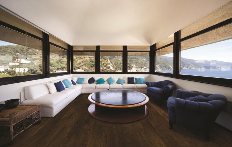 dark wood floor round wood table contemporary white sofa dark dark blue couches spacious glass window rattan table