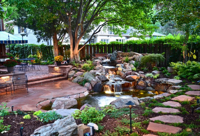 design footpath made by stone water feature stones lamp fence chairs table floor trees flowers brick wall