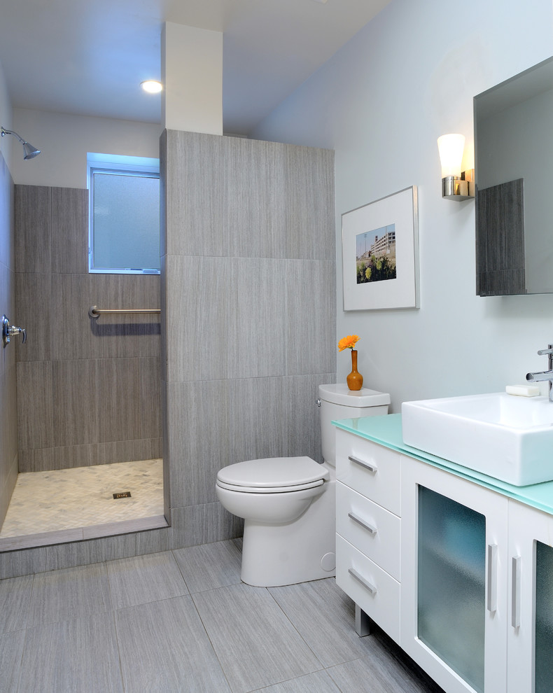 doorless shower space with beige tiles floors bathroom vanity with turquoise countertop white cabinets and free standing square sink in white white toilet white tiles floors for walk in shower