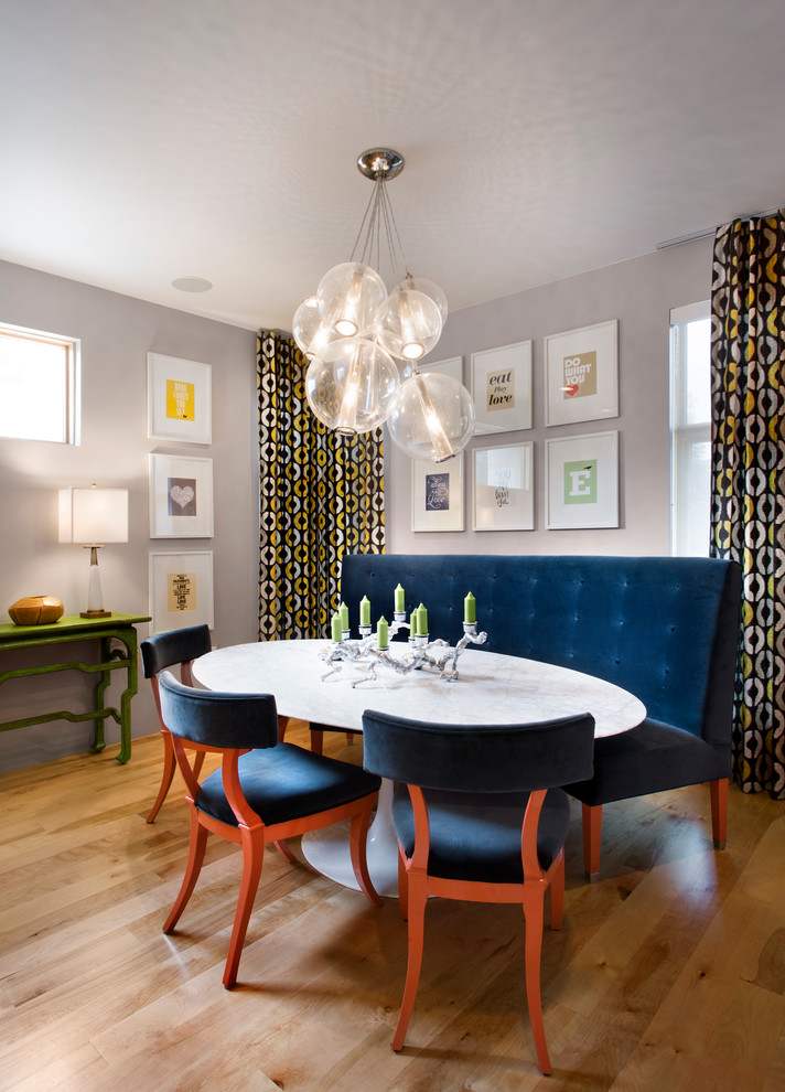elegant banquette set with blue velvet upholstered sofa and shairs, round white table, glass baloon pendants