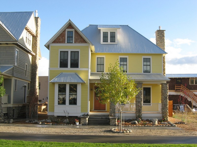 exterior paint with yellow on the wall, blue on the roof, browsn on the siding, brown on the door, white on the window frames