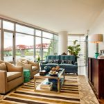 Family Room In A Condo With Rugs, Brown Chairs, Green Sofa, Floor Reading Lamp, Table Lamp. Dark Wood Cabinet, Glass Coffee Table, Painting