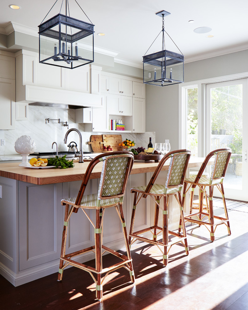 farmhouse kitchen remodel with white cabinetry wood top kitchen island and stools white marble backsplash deep toned pendant lamps