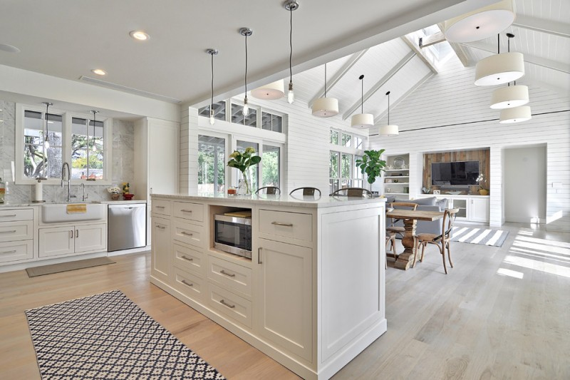 farmhouse open kitchen with brown wooden flooring, white wall and ceiling, vaulted ceiling for the dining area, white cabinet for the kitchen