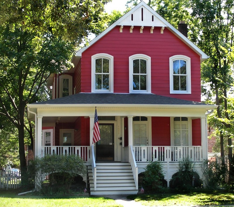 farmhouse with vibrant red siding exterior and old look railings wrapped the front porch