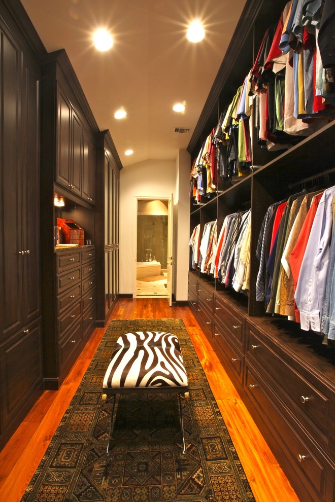 floor to ceiling closet dark wooden cabinet spacious hanging clothes space wooden floor tribal patterned carpet