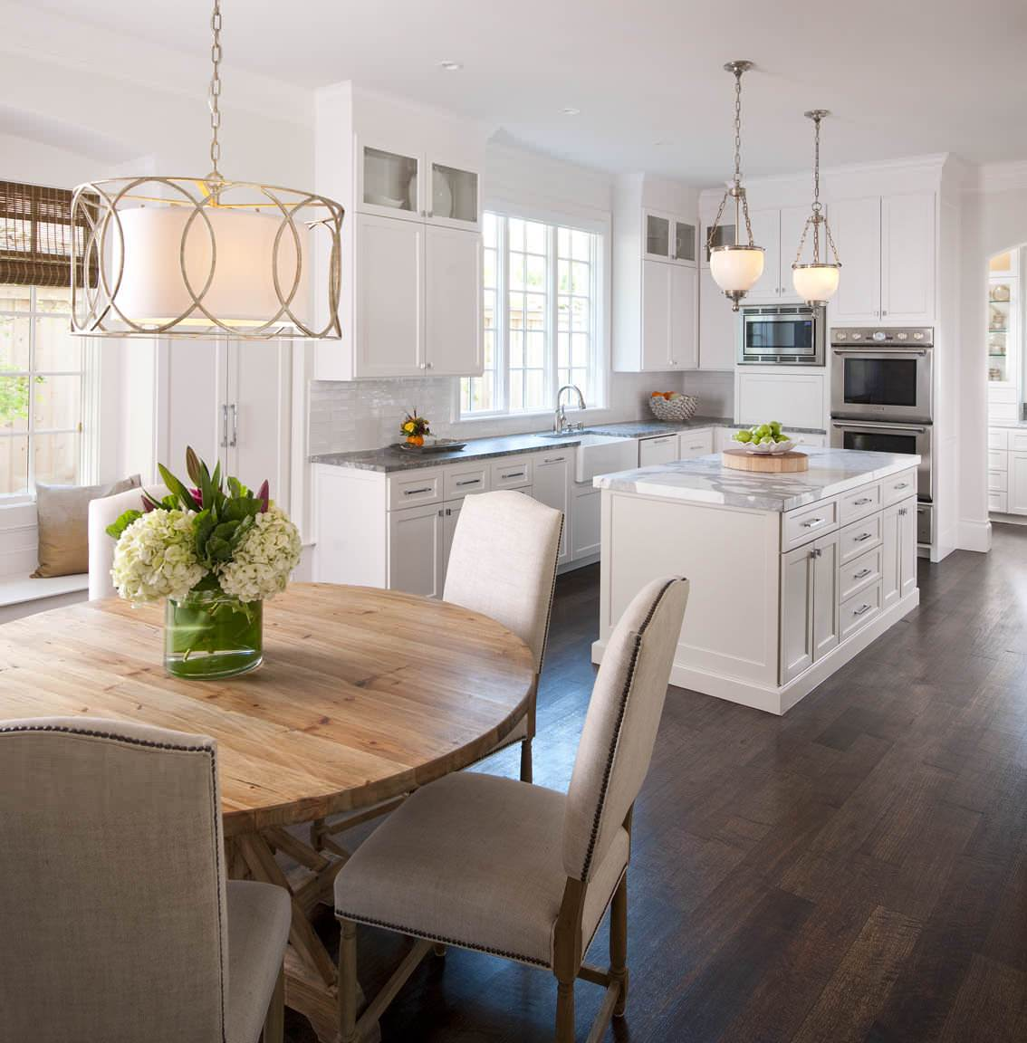 floor to ceiling white cabinet granite countertop wooden rounded dining table dark hardwood floor pendant lights