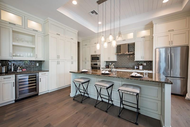 floor to ceiling white cabinet pendant lights marble counter top wooden floor brick backsplash bar stools