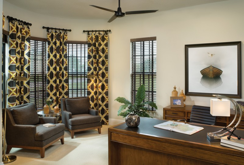 full length half way curtains in dark & gold tones a set of dark toned working desk and black working chair a pair of dark brown chairs light beige walls and floors black window shutters