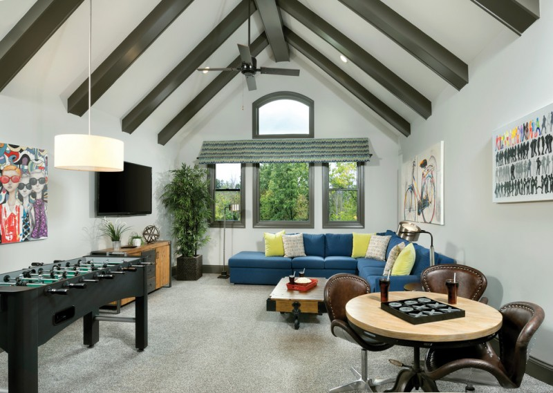 game room in vaulted ceiling room with foosball table, round table with leathered chairs, blue velvet sofa, yellow blue white pillows, brown cabinet