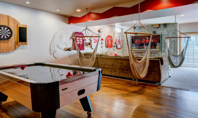 game room with darts, game table, television, living room, team jersey hangings