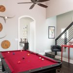 Game Room With Red Black Billiard Table, Red Stool Black Stools, Red Table, Rug, Wall Mounted Animal's Head, Black Ceiling Fan