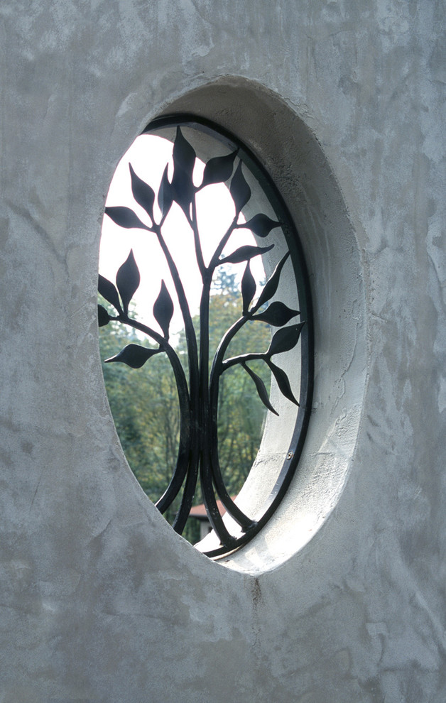 garden wall's exterior window with black iron wrought tree ornament