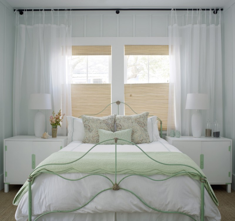 grand white half curtains with black wrought iron rods white minimalist bedside tables green painted bed with head and feetboard bamboos window shades