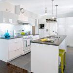 grey quartz countertop white kitchen chair floor tile wood cabinets stove window glass faucet sink lamps