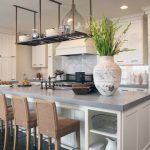 grey quartz countertop white kitchen dark floor dining chairs clock lamps cabinets dining table rack shelf