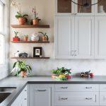grey quartz countertop white kitchen floor tile hanging lights wall cabinets wall tiles shelves window glass
