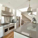grey quartz countertop white kitchen metallic color wood floor stove wall cabinet ceiling lamp hanging lights railing