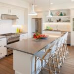 grey quartz countertop white kitchen wood floor chairs shelves cabinet hanging lamps stove appliances wall storage