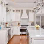 Grey Quartz Countertop White Kitchen Wood Floor Chairs Stove Appliances Wall Cabinets Doors Crystal Lighting