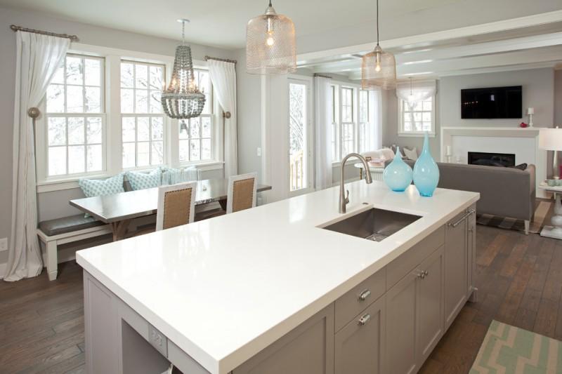 grey quartz countertop white kitchen wood floor faucet sink sofa pillows hanging lamps windows glass lighting wall tv