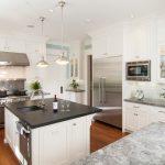 grey quartz countertop white kitchen wood floor hanging lamps cabinets stove towel rack faucet sink glass door
