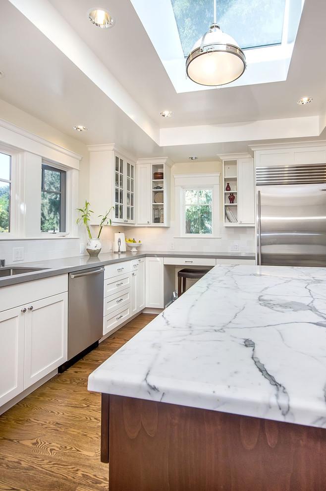 grey quartz countertop white kitchen wood floor hanging light window glass cabinet shelves drawers appliances