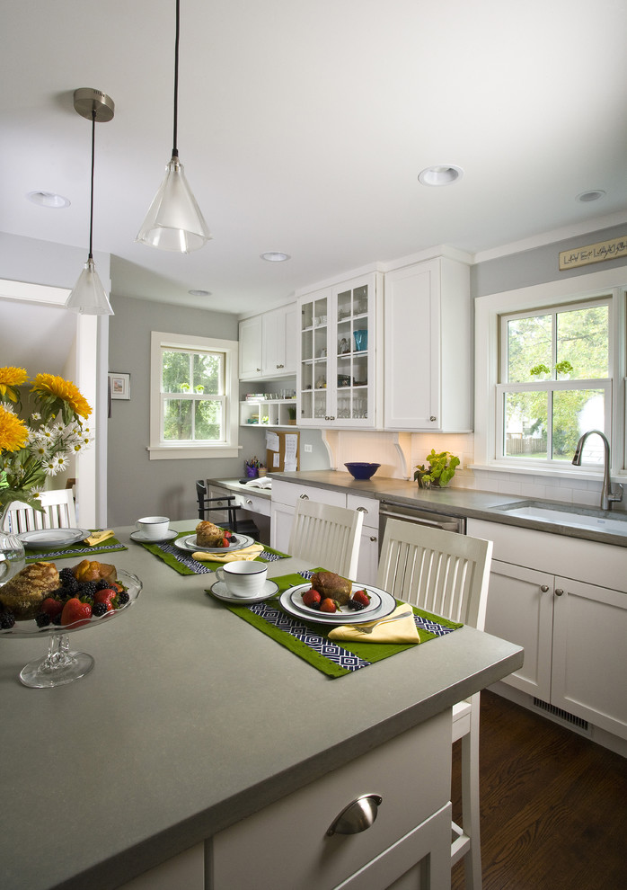 grey quartz countertop white kitchen wood floor hanging lights flowers chairs cabinets faucet sink windows cabinets lamps