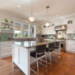 Grey Quartz Countertop White Kitchen Wood Modern Dining Chairs Cabinets Stove Hanging Lights Windows Shelves Clock