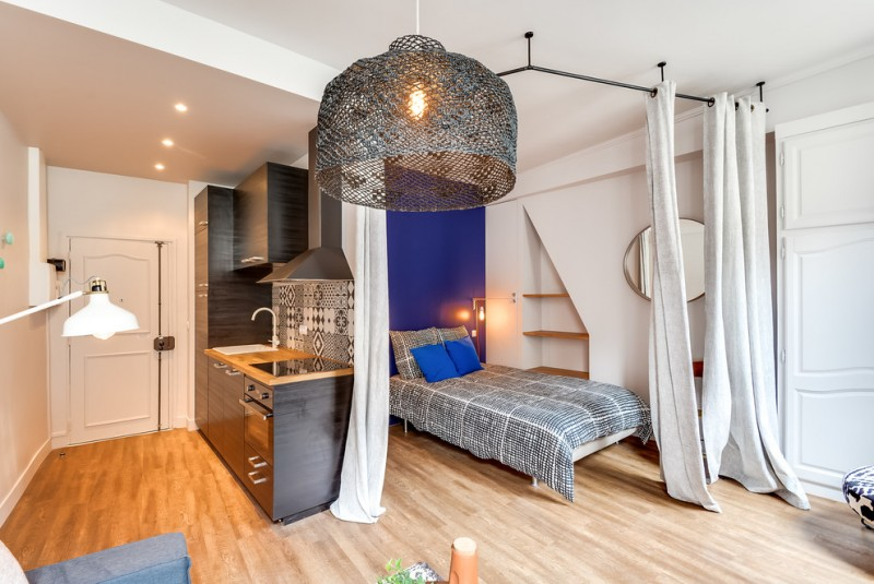 grey single bed in private are with curtain in studio apartment