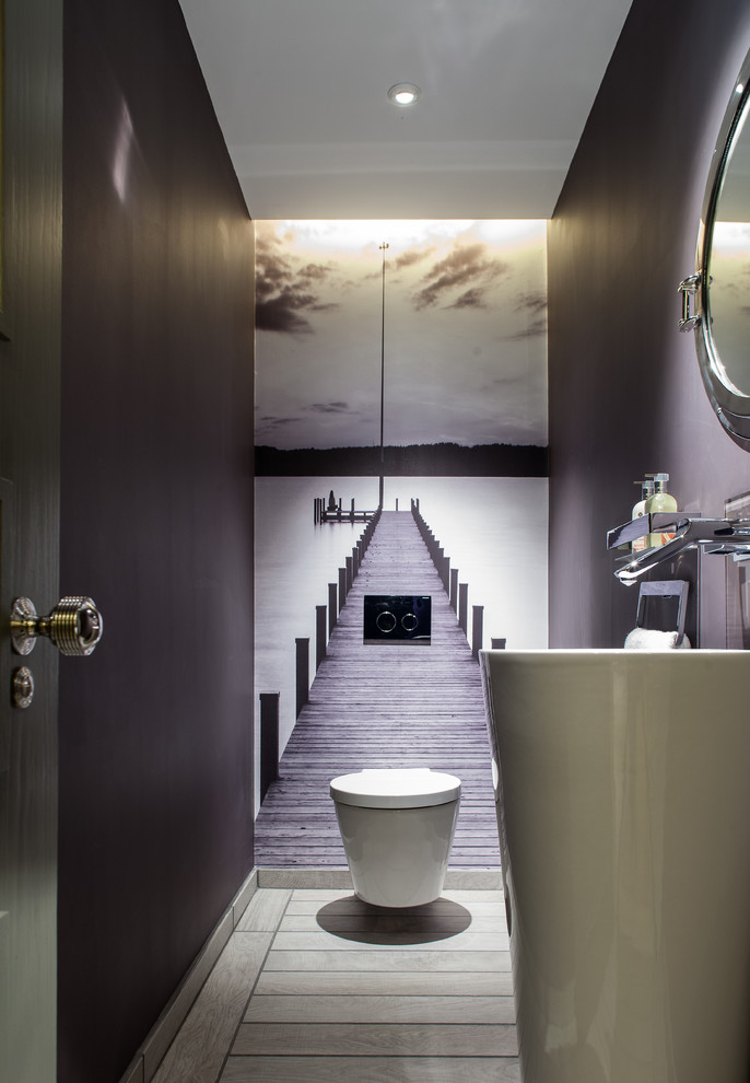 half bathroom with grey painted wall, wallpaper with long bridges picture in the back, white toilet, white long round sink