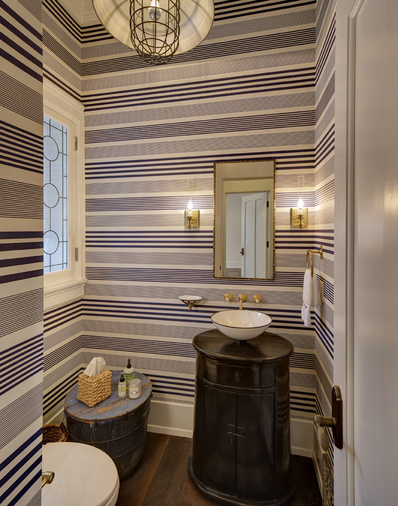 half bathroom with white and black stripes wallpaper up to ceiling, black cylinder cabinet with white bowl sink on top, rustic blue wooden pail, white toilet, rustic white lamp