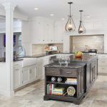 kitchen flooring wall tv glass wall cabinets books cups drawers sink faucet seating hanging lamp travertine floor