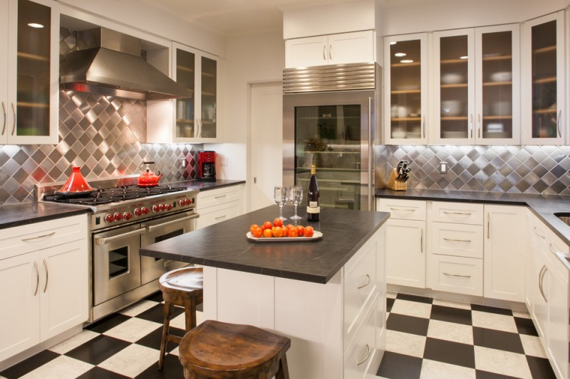 kitchen with white wall, cabinet, black counter top, checkerboard flooring