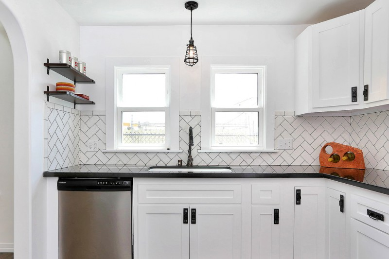 kitchen with white wall, window pane, cabinet, ceramic half wall, black counter top